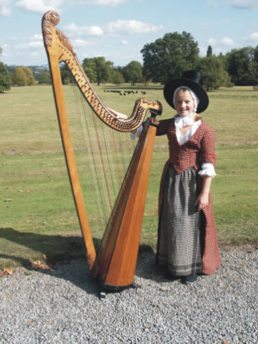 Photograph of Lady Llanover's Great-Great-Great-Great Grand-Daughter wearing her ancestors original costume with a Llanover Triple Harp.